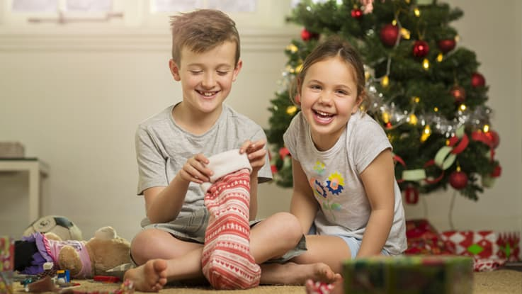 Two kids opening Christmas presents