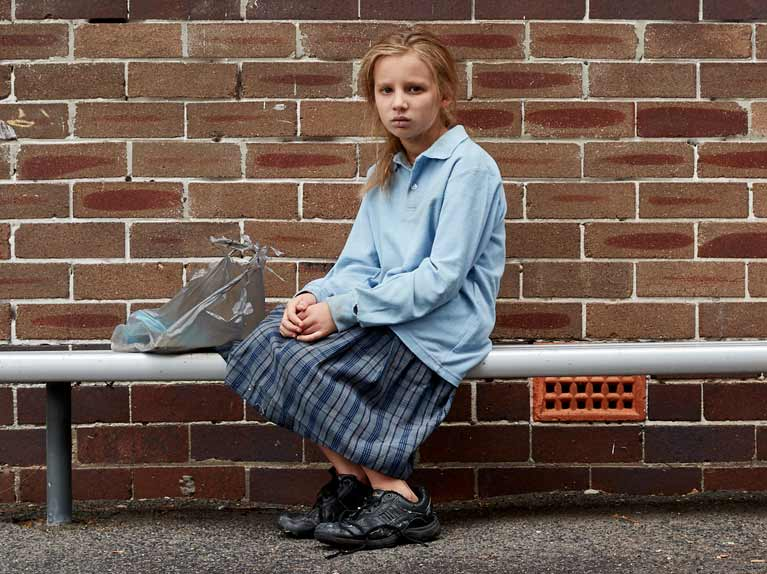 School girl sitting alone in playground