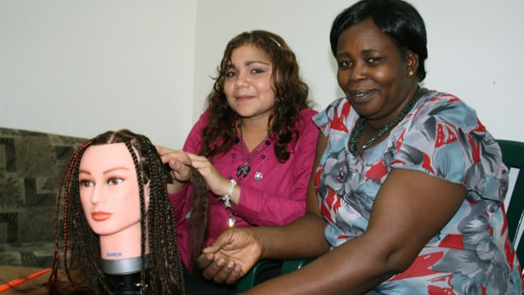 Student learning hair braiding at an African salon