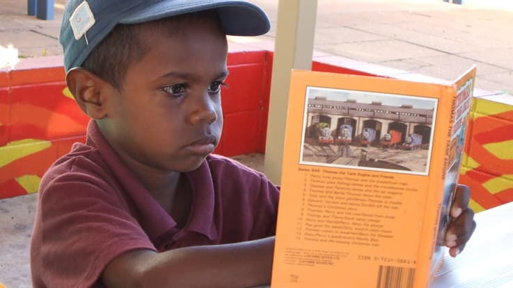 Boy reading a book in Katherine