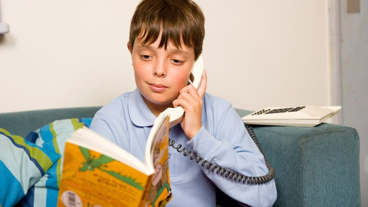 Boy sitting on couch reading over the phone