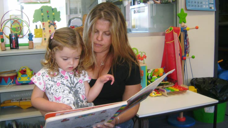 Mother and daughter sitting in a chair reading