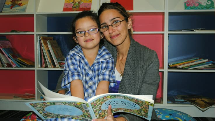 Mother with daughter in her school uniform reading